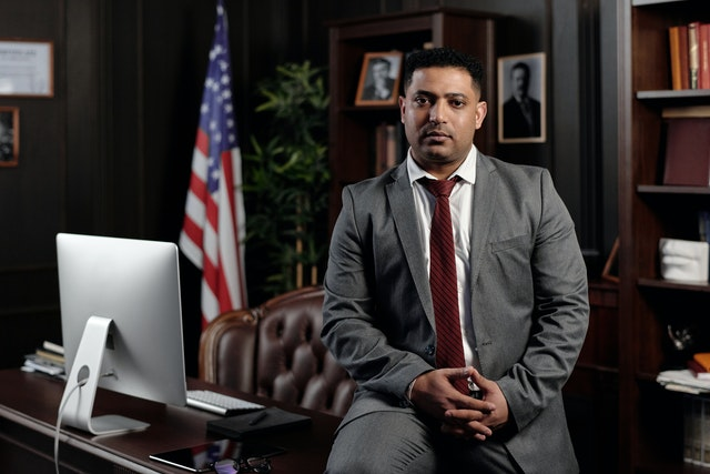 A criminal defense attorney poses on the corner of his desk with an american flag in the background