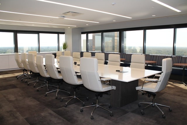 A board room sits empty as a lawyer appropriately weighs the risks of serving as both a board member and corporate lawyer